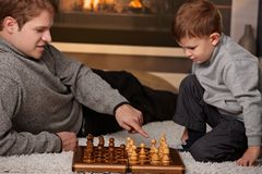 Father and son playing chess. Father and 4 years old boy playing chess at home in a cold winter day Stock Photography