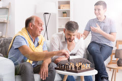 Father and son playing chess. Boy watching them and smiling royalty free stock image