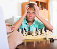 Father and son playing chess. At home stock images