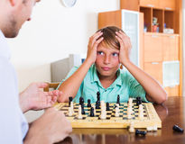Father and son playing chess. At home, boy losing stock photo