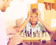 Father and son playing chess Stock Image