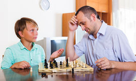 Father and son playing chess at home Royalty Free Stock Images