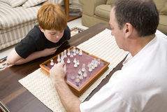 Father and son playing chess indoors. A father and ten year old son playing chess indoors royalty free stock images