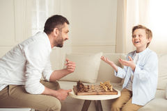 Father and son playing chess and looking at each other at home. Emotional father and son playing chess and looking at each other at home royalty free stock images