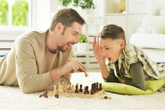 Father and son playing chess. Portrait of happy father and son playing chess stock photos