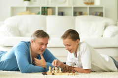 Father and son playing chess. Portrait of happy father and son playing chess royalty free stock photo