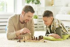 Father and son playing chess. Portrait of happy father and son playing chess royalty free stock photos