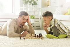 Father and son playing chess. Portrait of happy father and son playing chess stock photography