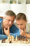 Father and son playing chess. Portrait of happy father and son playing chess royalty free stock images