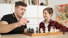 Father and son are playing chess and smiling while spending time together at home slow motion stock video footage