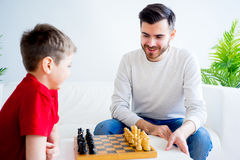 Father and son playing chess. Father and son are playing chess together royalty free stock photography