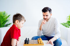 Father and son playing chess. Father and son are playing chess together stock image