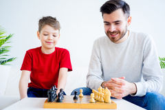Father and son playing chess. Father and son are playing chess together stock images