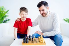 Father and son playing chess. Father and son are playing chess together royalty free stock photo