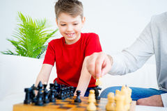 Father and son playing chess. Father and son are playing chess together royalty free stock images