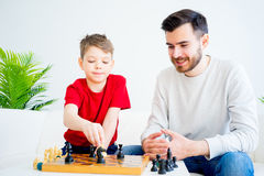 Father and son playing chess. Father and son are playing chess together royalty free stock image