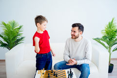 Father and son playing chess Stock Photo