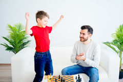 Father and son playing chess. Father and son are playing chess together stock photo