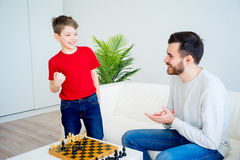 Father and son playing chess. Father and son are playing chess together stock photos