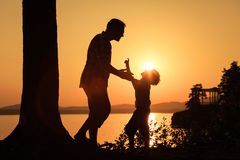 Father and son playing on the coast of lake Stock Image