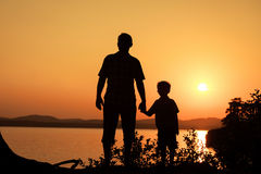 Father and son playing on the coast of lake Royalty Free Stock Photos