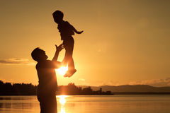 Father and son playing on the coast of lake Stock Photo