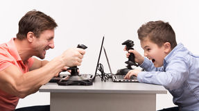 Father and son playing the computer games Stock Photos