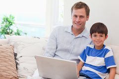 Father and son playing computer games together. Young father and son playing computer games together Royalty Free Stock Photography
