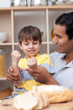 Father and son playing cutting bread Stock Images