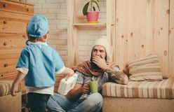 Father and son playing doctor, healthcare and treatment concept. Emergency medical specialist visiting patient at home. Man with long beard in knitted white stock image