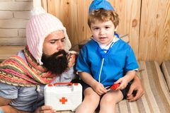 Father and son playing doctor at home. Dad and kid dressed as nurse. Medicine and health. Physician with serious face. Giving instructions to bearded man royalty free stock images
