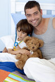Father and son playing doctors in bed Stock Images