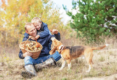 Father with son playing with dog on autumn forest glade Royalty Free Stock Photos