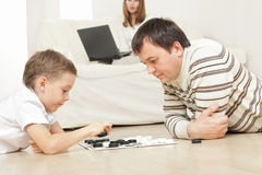 Father with the son playing draughts Stock Images