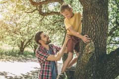 Father and son are playing with each other. Guy is supporting his child. Boy is looking down at father. They are smiling. Both of them are happy Stock Photos