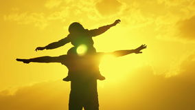 Father and son playing in the evening sky silhouette. Of two people stock footage