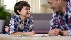 Father and son playing exciting board game, parent developing boys skills. Stock photo stock photo