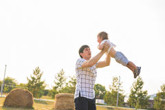Father and son playing on the field at the day time. People having fun outdoors. Concept of friendly family.  Stock Images