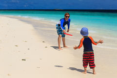 Father and son playing with flying disc at beach Stock Photography