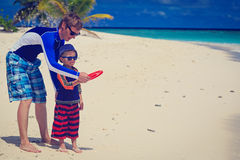 Father and son playing with flying disc at beach Stock Image