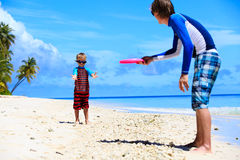 Father and son playing with flying disk at beach Stock Photo