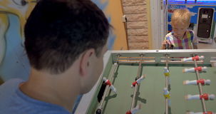 Father and Son Playing Foosball in Arcade. High-angle shot of father and little son playing foosball in arcade stock video