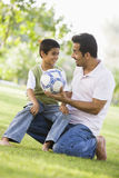 Father and son playing football. Father and son playing in park Stock Image