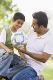 Father and son playing football. In park Royalty Free Stock Photo