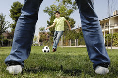 Father and son playing football. In urban park, concept of entertainment and education Royalty Free Stock Photo