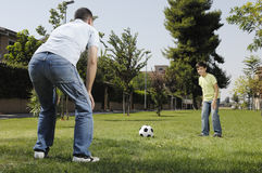 Father and son playing football. In urban park, concept of entertainment and education Royalty Free Stock Photography