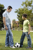 Father and son playing football. In urban park, concept of entertainment and education Royalty Free Stock Images