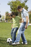Father and son playing football. In urban park, concept of entertainment and education Royalty Free Stock Photos