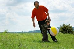 Father and son playing football. On nature Stock Image