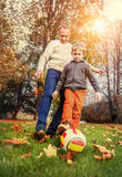 Father with son playing in football at the autumn park Stock Images